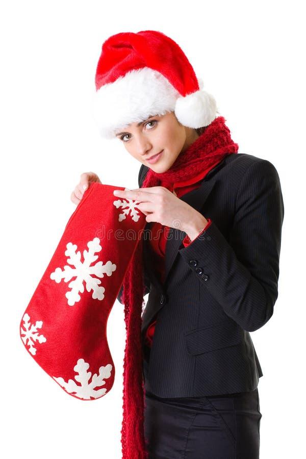 Femme d'affaires dans le chapeau de Santa avec la chaussette rouge de Noël image libre de droits