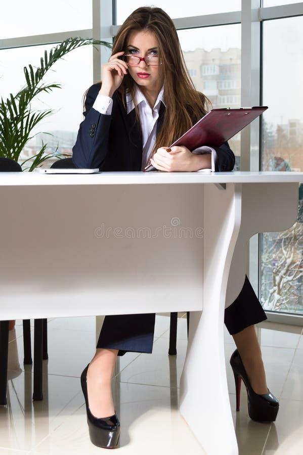 Femme d'affaires dans le costume de l'homme se reposant à la table de bureau et regardant au-dessus des verres image stock