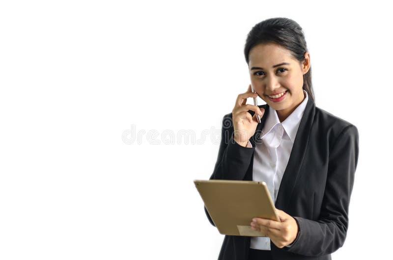 Femme d'affaires dans le costume formel tenant le taplet et téléphone communiquant sur le fond blanc images stock