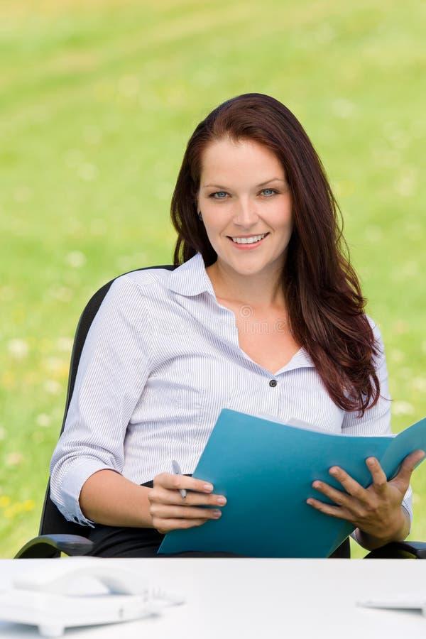 Femme d'affaires dans le dépliant attrayant de sourire de nature photographie stock libre de droits