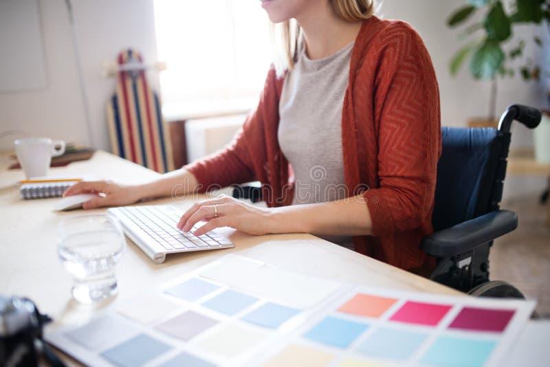 Femme d'affaires dans le fauteuil roulant au bureau dans son bureau photo stock