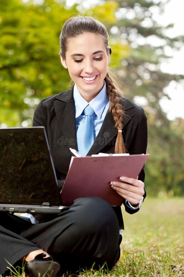 Femme d'affaires dans le procès travaillant à l'herbe photo stock