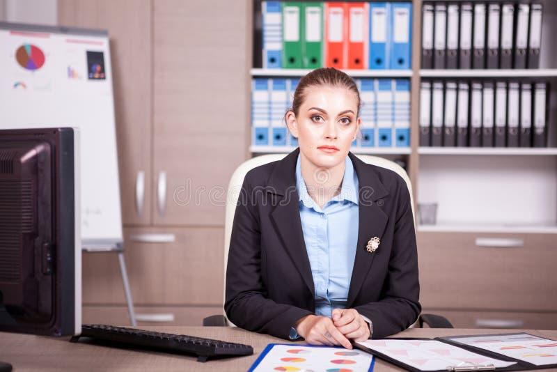 Femme d'affaires dans un bureau avec des diagrammes sur la table photos libres de droits