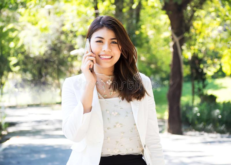 Femme d'affaires de Beautyful marchant et à l'aide du téléphone intelligent en parc photos stock