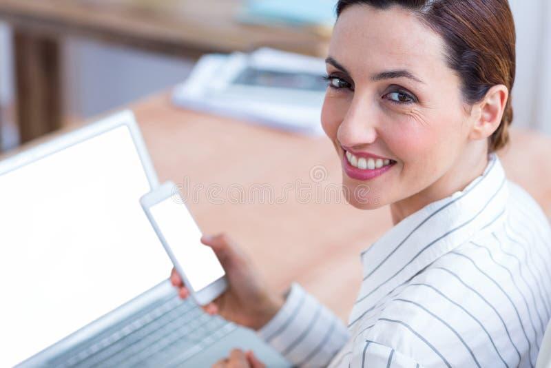 Download Femme D'affaires De Brune Souriant Utilisant L'ordinateur Portable Et Son Mobile Photo stock - Image du cahier, bureau: 56483718