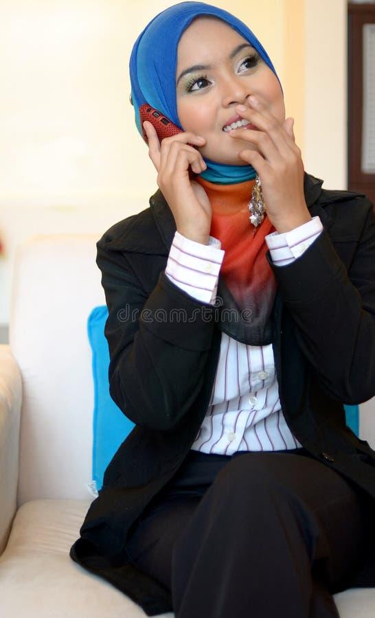 Femme d'affaires de Muslimah dans l'écharpe principale avec le téléphone portable photographie stock libre de droits