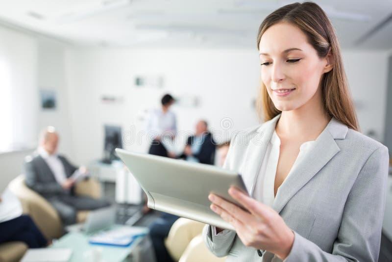 Femme d'affaires de sourire à l'aide du comprimé numérique dans le bureau photographie stock