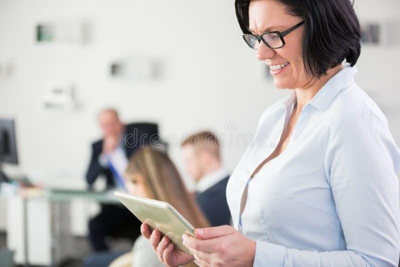 Femme d'affaires de sourire à l'aide du comprimé numérique dans le bureau photo libre de droits