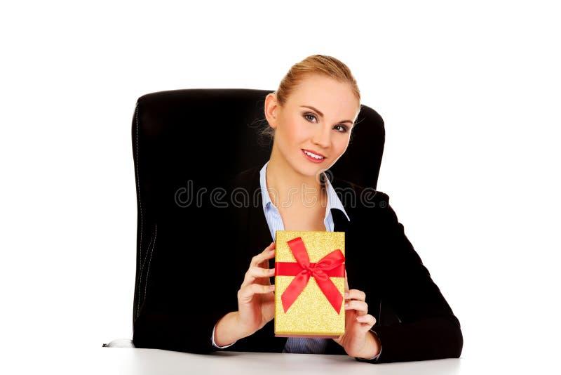 Femme d'affaires de sourire avec le boîte-cadeau se reposant derrière le bureau photo stock