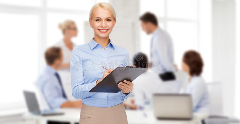 Femme d'affaires de sourire avec le presse-papiers et le stylo photos stock