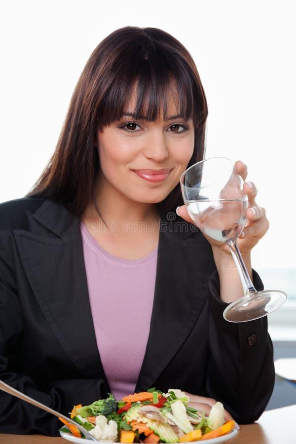 Femme d'affaires de sourire ayant la glace de l'eau photo stock