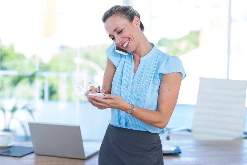 Femme d'affaires de sourire ayant un appel téléphonique et prendre des notes photos stock