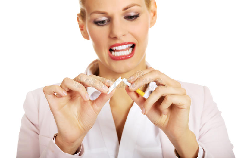 Femme d'affaires de sourire cassant une cigarette photos stock