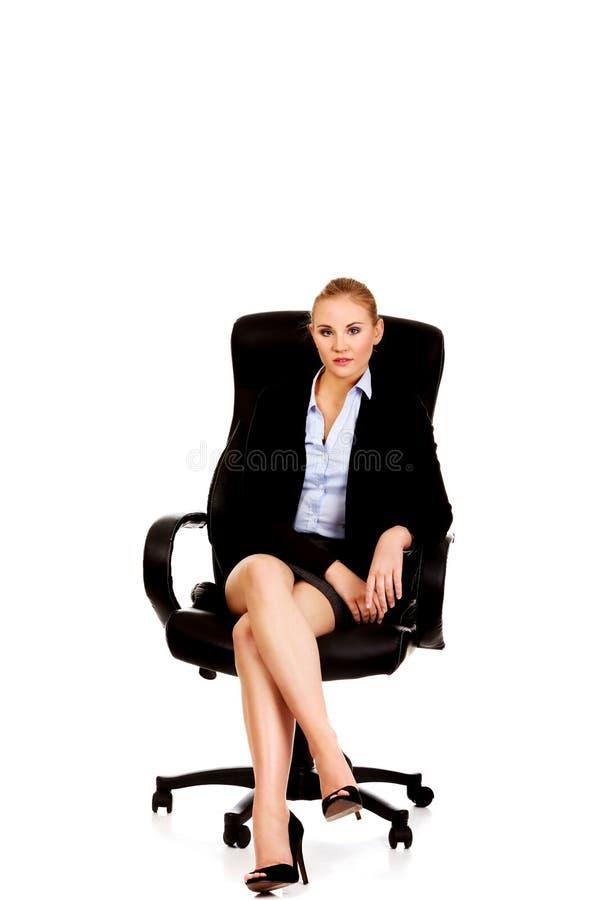 Femme d'affaires de sourire de jeunes s'asseyant sur une chaise dans le bureau image stock