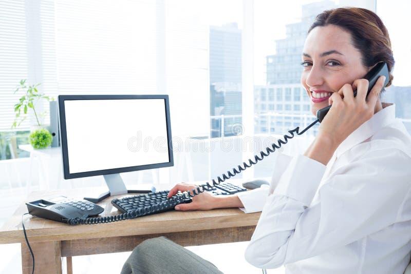 Download Femme D'affaires De Sourire Employant L'ordinateur Et Téléphoner Image stock - Image du photo, appareil: 56481733