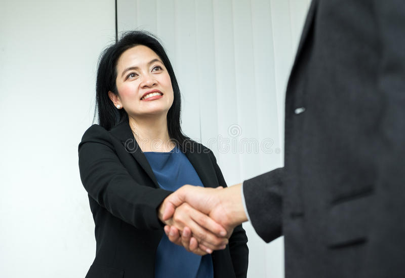 Femme d'affaires de sourire et homme d'affaires serrant la main dans le bureau, PA photos stock