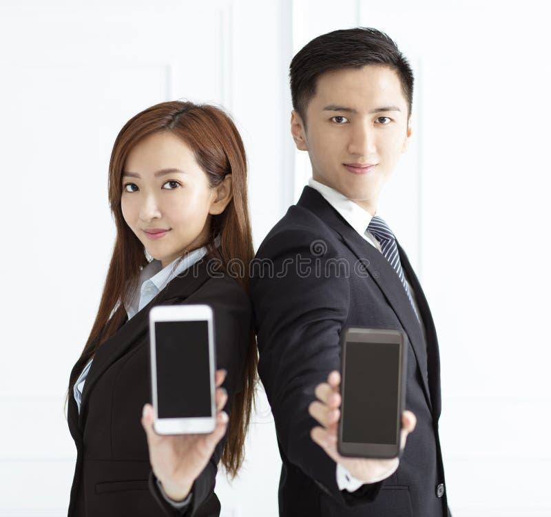 femme d'affaires de sourire et t?l?phone intelligent d'apparence d'homme d'affaires image libre de droits