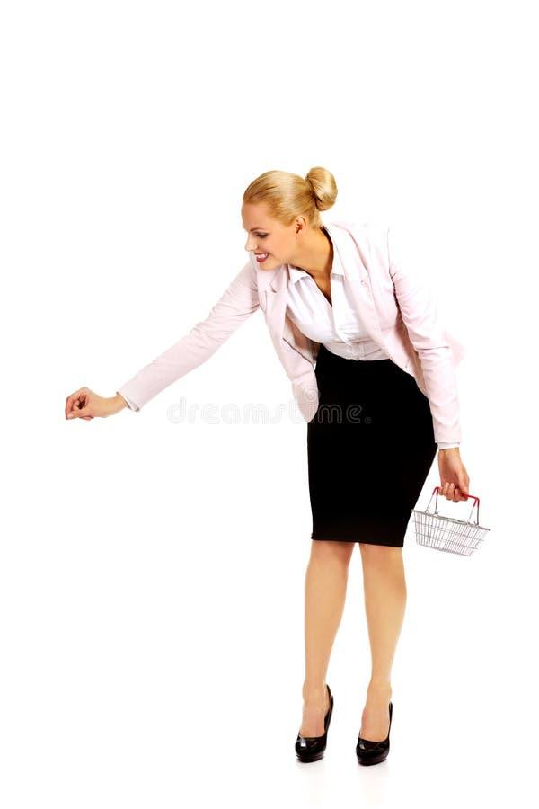 Femme d'affaires de sourire faisant le petit panier d'achats et de participation image stock