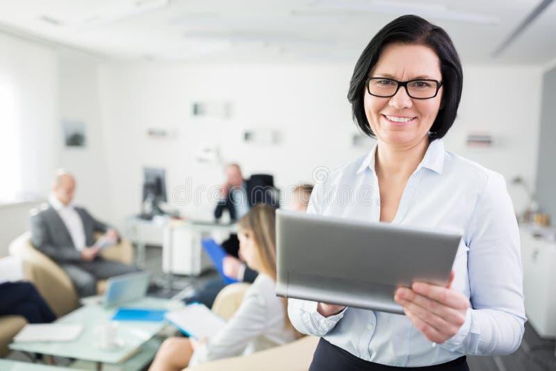 Femme d'affaires de sourire Holding Digital Tablet dans le bureau photographie stock
