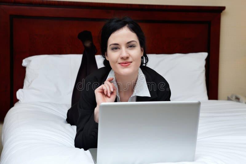 Femme d'affaires de sourire Lying sur le lit avec l'ordinateur portable photos libres de droits