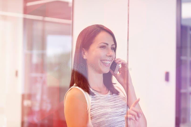 Femme d'affaires de sourire parlant au t?l?phone portable au bureau image libre de droits