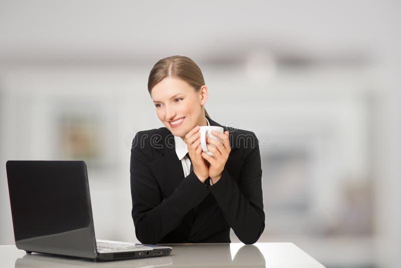Femme d'affaires de sourire s'asseyant avec l'ordinateur portable, retenant le café et la tasse de thé photographie stock libre de droits