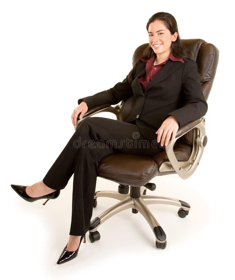 Femme d'affaires de sourire s'asseyant sur une présidence en cuir photos libres de droits