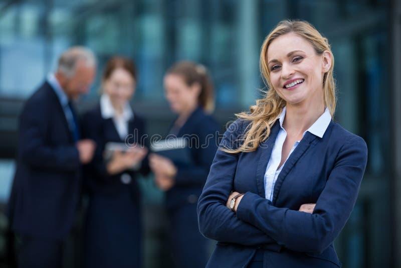 Femme d'affaires de sourire se tenant avec des bras croisés images stock