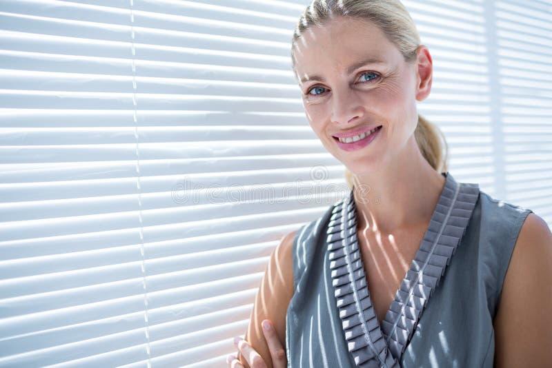Download Femme D'affaires De Sourire Se Tenant Dans Le Bureau Photo stock - Image du adulte, sourire: 56483116
