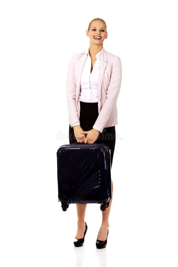 Femme d'affaires de sourire soulevant sa valise photo libre de droits
