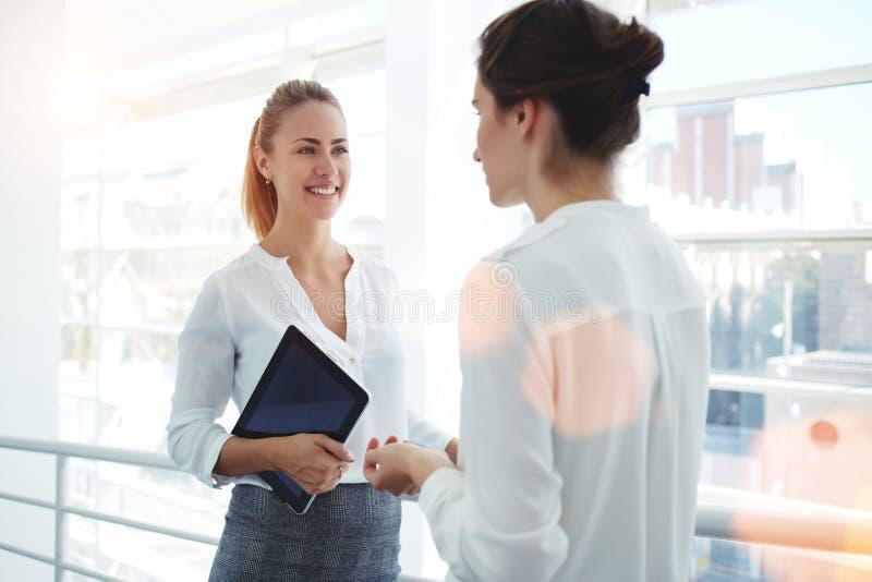 Femme d'affaires de sourire tenant le comprimé numérique et parlant avec l'associé tout en se tenant dans l'intérieur moderne de  image stock
