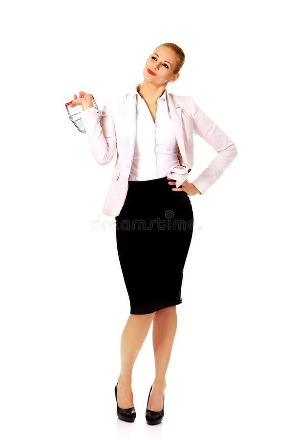 Femme d'affaires de sourire tenant le petit panier à provisions photos libres de droits
