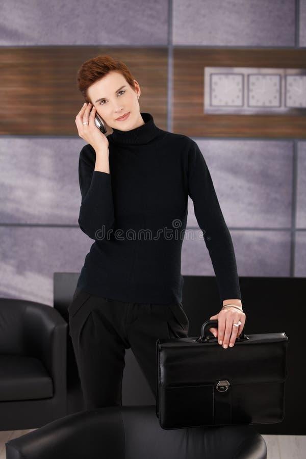 Femme d'affaires dernier cri prenant l'appel mobile photo stock