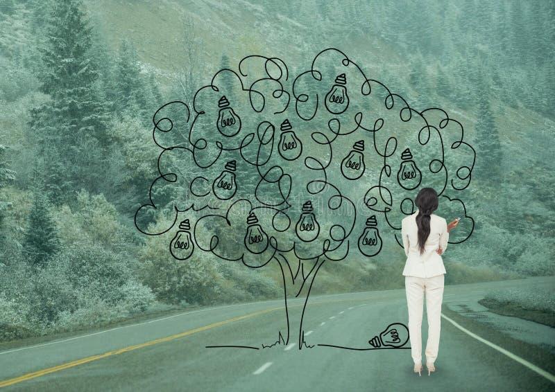 Femme d'affaires dessinant un arbre sur la route photo stock