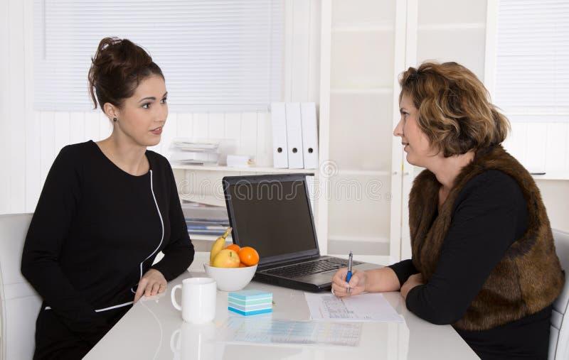 Femme d'affaires deux s'asseyant au bureau parlant ensemble photographie stock libre de droits