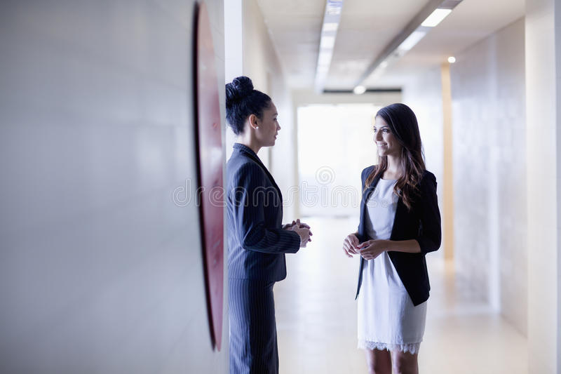 Femme d'affaires deux se tenant dans le couloir et parler photos libres de droits