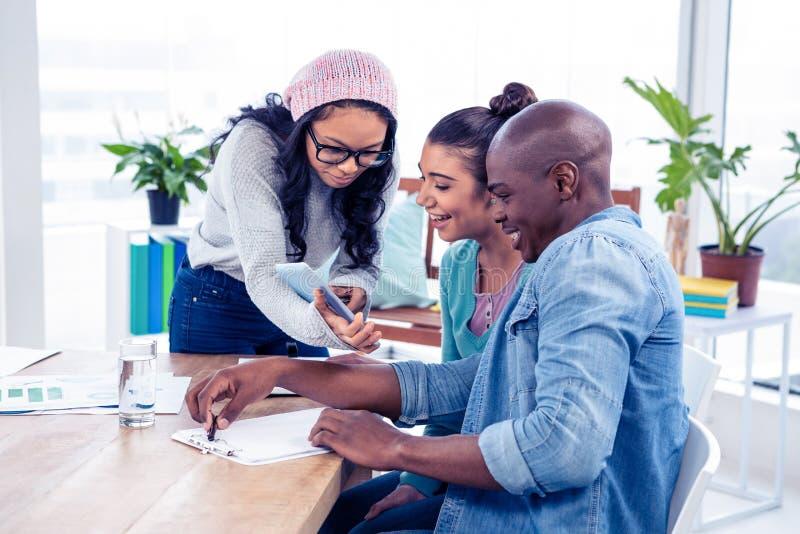 Femme d'affaires discutant avec des collègues au-dessus de comprimé numérique photos stock