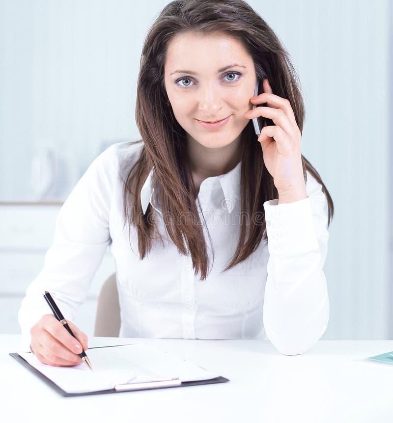 Femme d'affaires discutant des documents de travail ? un t?l?phone portable images stock