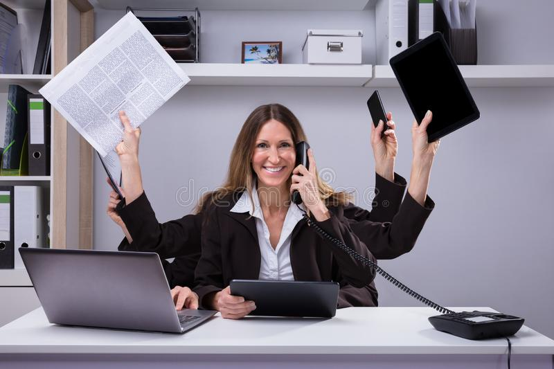 Femme d'affaires Doing Multitasking Work dans le bureau image libre de droits