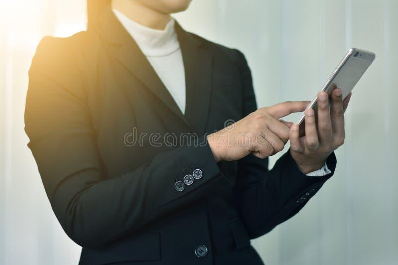 Femme d'affaires elle emploie l'Internet au téléphone intelligent photo stock