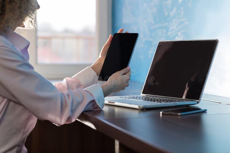 Femme d'affaires employant la Tablette et la femme d'affaires de dactylographie Sitting Desk In Coworking d'ordinateur portable t photographie stock libre de droits