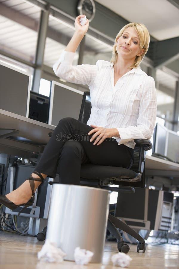Femme d'affaires en ordures de projection de bureau dans le coffre photographie stock libre de droits