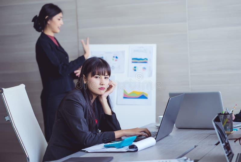 Femme d'affaires ennuyée à la présentation avec des collègues en rencontrant r images stock