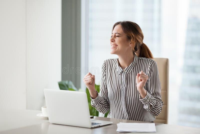 Femme d'affaires enthousiaste faisant des gestes célébrant le succe en ligne de société photographie stock libre de droits