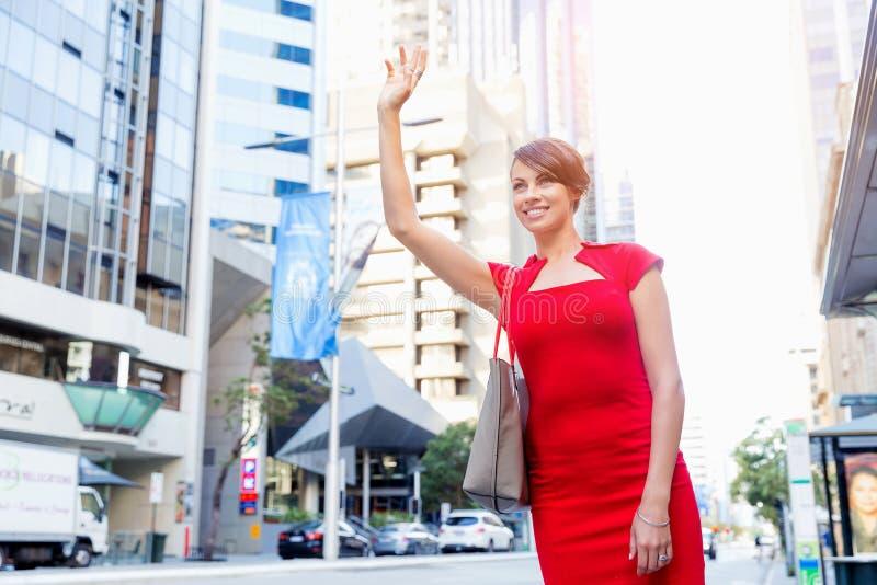 Femme d'affaires essayant d'attraper un taxi photo stock