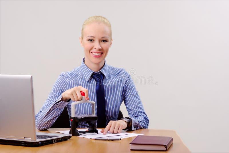 Femme d'affaires estampant des documents images stock