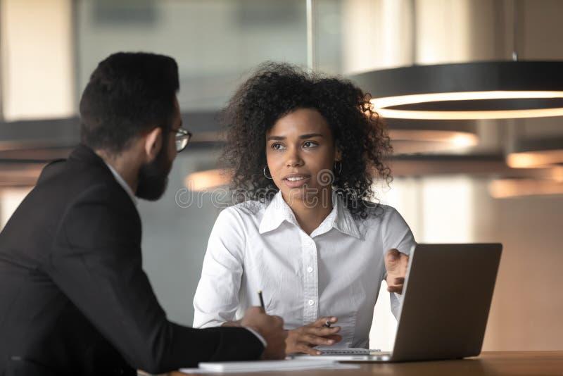 Femme d'affaires et collègue de race mixte discutant du projet, en utilisant un ordinateur portable photo libre de droits