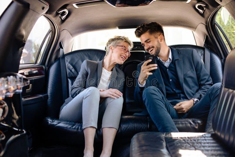 Femme d'affaires et homme d'affaires ayant le rire dans la limousine images stock