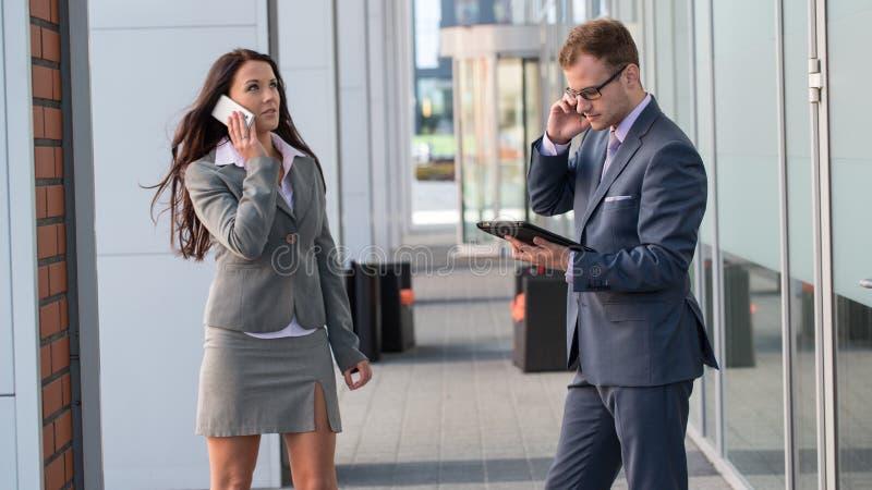 Femme d'affaires et homme d'affaires travaillant dehors avec le PC de téléphone portable et de comprimé. image stock