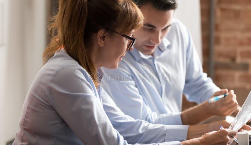 Femme d'affaires et homme d'affaires discutant des écritures tenant des documents lors de la réunion d'affaires photos stock